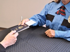 Airport Security Personnel Examining a Passenger's Travel Documents